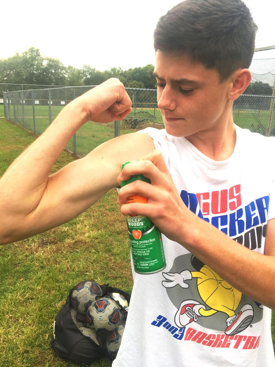 Nathan Faupel '21 sprays bug spray to protect against EEE