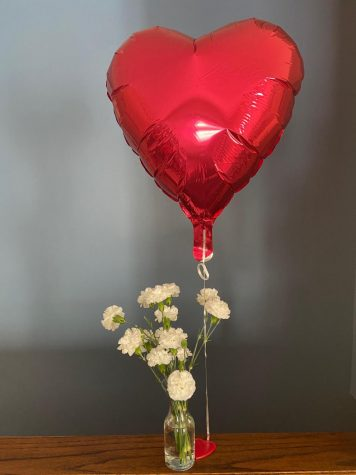ballon that is shaped like a heart and flowers on a table